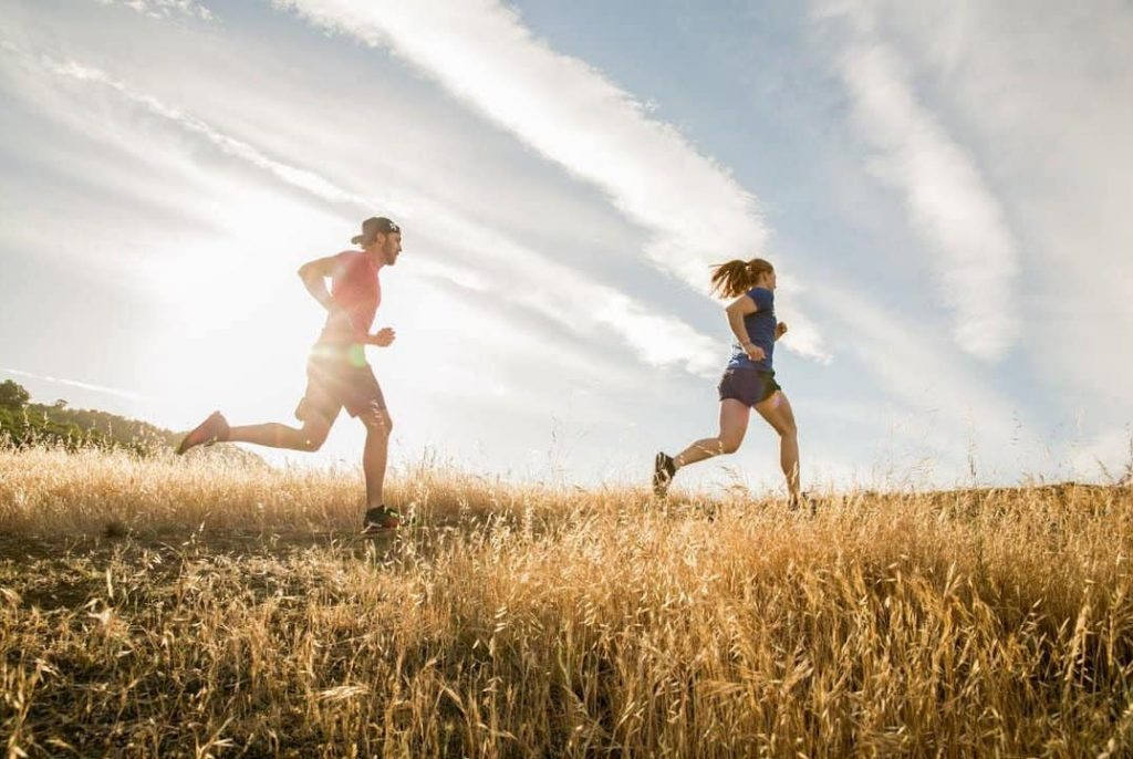 two people running across a field with good form.