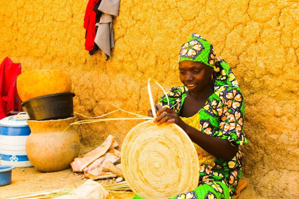 Woman weaving a basket in Kano, Nigeria, one of the homes of the African language Hausa.