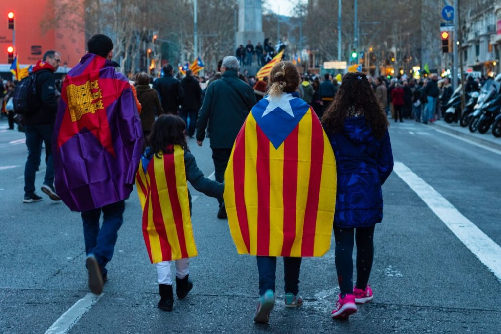 People walking streets in Catalunya wearing the Catalan flag