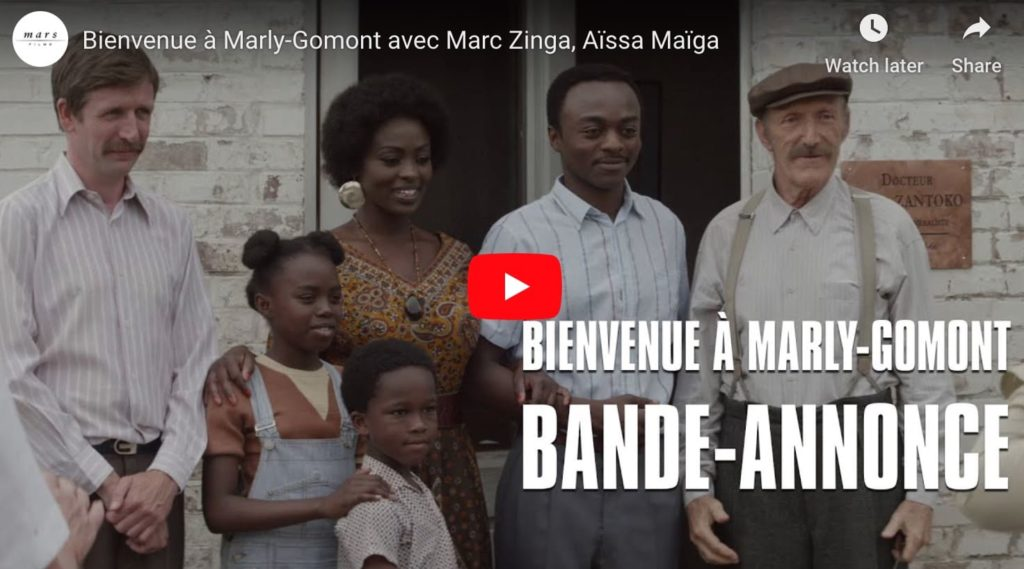 Screen capture from french film Bienvenue a Marly Gomont, a film about racism, showing a black family amidst white people