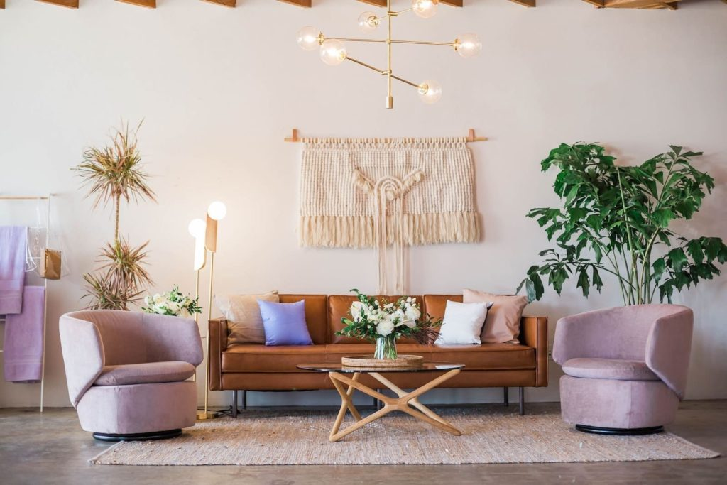 nice living room with lights, pot plant, coffee table and pink furniture
