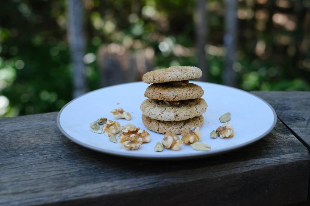 Persian walnut cookies on a plate with trees in the background