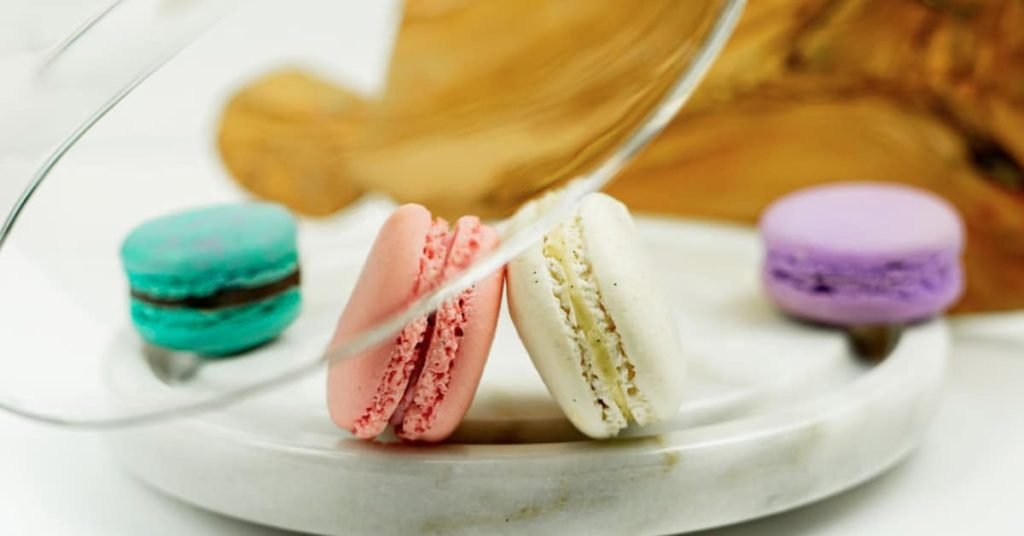 say please in french to these macarons of different colours on a plate.